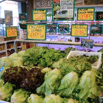 leafy greens being sold in a market with price signs