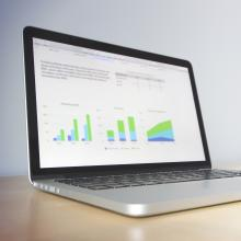 laptop with charts and graphs on the screen